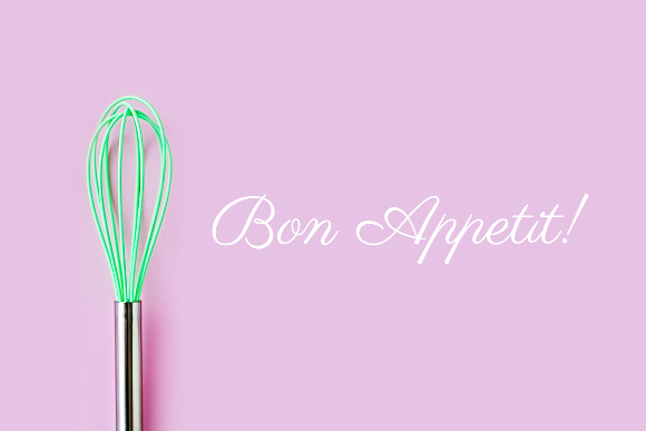 Green culinary whisk on colored background. 'Bon Appetit' - enjoy your meal quote. Creative thinking ideas, cooking concept